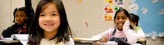 Header Image 05 - Elementary Girls in Class - focus on the faces of a few...